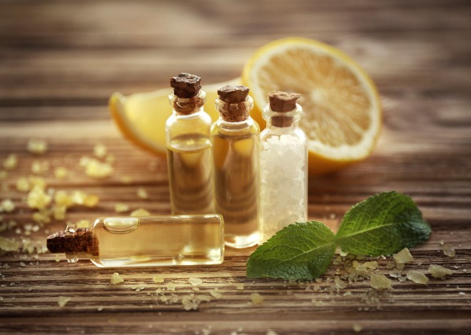 Beautiful spa composition with lemon essential oil on wooden background, closeup